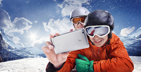 Sport and travel backgrounds. Winter, ski, snow and fun - family enjoying ski holiday. Mobile photo. Selfy.