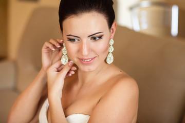 Brunette bride holding earrings in morning. Wedding jewelry