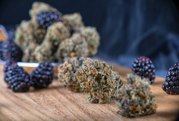 Cannabis buds (Berry Noir strain) with fresh fruit - medical mar