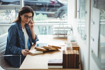 Business executive talking on mobile phone while looking at stones slab in office