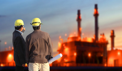 engineering man standing against oil refinery plant in heavy petrochemical industrial estate , industry 4.0 concept