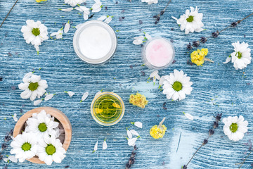 organic cosmetics with camomile on blue background top view