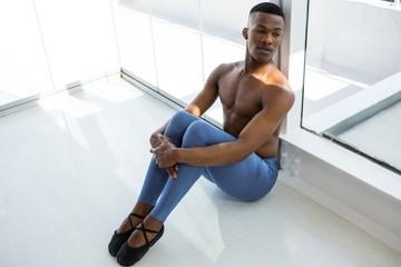 Thoughtful ballerino sitting on floor