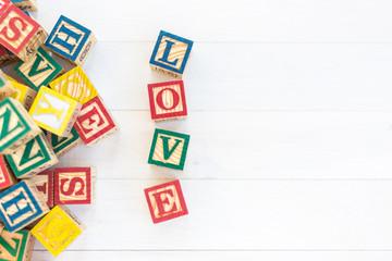 LOVE write in wooden alphabet block on white wooden background.