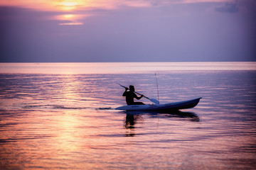 Silhouette of a man on a sea kayak on a colorful sunset