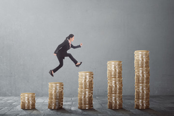 Young asian business woman climb up the gold coins