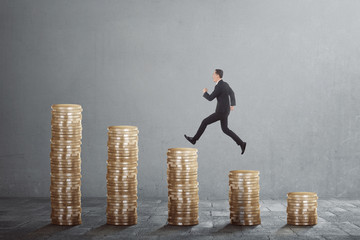 Happy asian businessman jump on between coin stacks