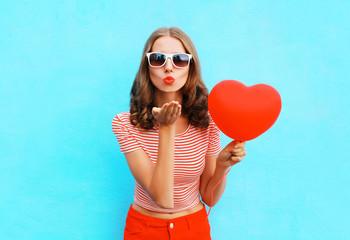 Portrait pretty woman sends air kiss with red balloon heart shap