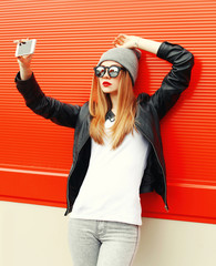Fashion girl taking self-portrait on smartphone in city over red