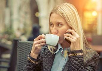 Woman seating in cafe with her phone and coffee.