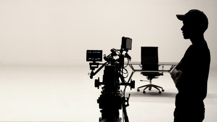 Behind the scenes of silhouette working people or video production film crew are making movie or shooting commercial with high quality professional equipment in studio.