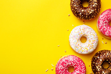 Flat lay donuts on a yellow background with copy space. Top view