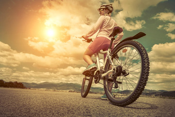 Beautiful woman in helmet and glasses stay on the bicycle under