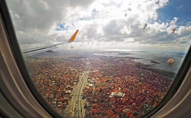 Aerial view through porthole of aircraft, flying over Istanbul city center with skyscraper buildings , Turkey