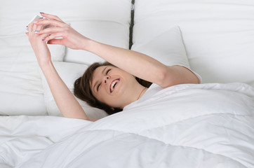 Beautiful girl in a white t-shirt is holding a phone in his hand lying on the bed