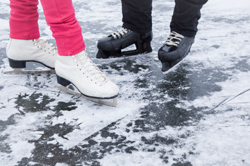 White and black skates on the lake ice in winter day. Weekends activities outdoor in cold weather.