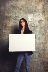 Serious business woman in modern clothes standing with a white canvas in the hands of. Horizontal mockup