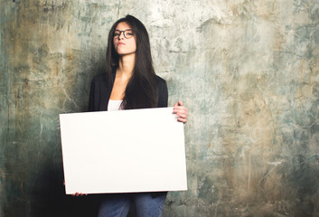 Charming business woman posing with a white canvas in the hands of. Horizontal mockup