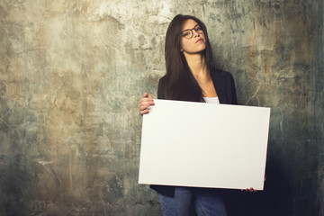 Modern business woman with glasses and jacket posing with a white canvas in the hands of. Horizontal mockup