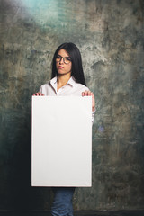 Girl with a thoughtful face and in modern clothes posing with a white canvas. Horizontal mockup
