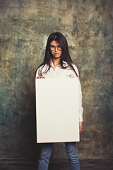 Beautiful girl smiling and posing in white business shirt and blue jeans with a white canvas. Horizontal mockup