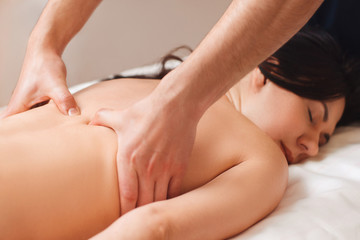 Chiropractor treating woman with pain in back. Young woman enjoying massage, free space. Body care, relax, health, alternative medicine, healthy spine, stress relief concept
