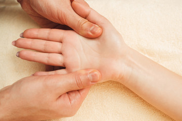 Female palm massaging flat lay closeup. Top view on masseur hand beating female hand and fingers. Health care, osteopathy, whole body massage, relax concept