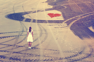 Woman in white dress stand alone on the sandy beach with red heart symbol and wheel trace curves. Vintage filter effect used.