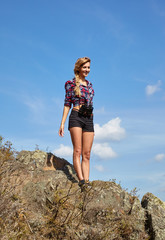 Young blonde woman tourist  in shirt and shorts  on a cliff on b