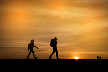 Silhouette of two backpackers (man and woman) who were traveling.The background image is a sunset in Thailand