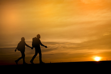 Silhouette of two backpackers (man and woman) who were traveling.The background image is a sunset in Thailand.Man and woman are walking hand in hand.