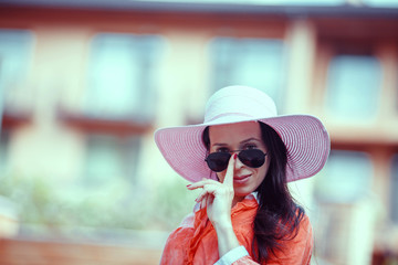 Beautiful young woman in elegant hat and sunglasses posing outdo