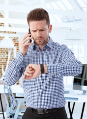 Businessman on mobile watching wristwatch anxious