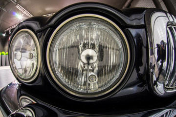 Close up high detailed view on headlights of black retro luxury car.