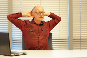 middle age balding man relaxing neck - stretching arms - short break for exercise on chair in office