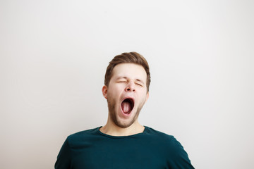 Yawing  young man on a light background Wall mural