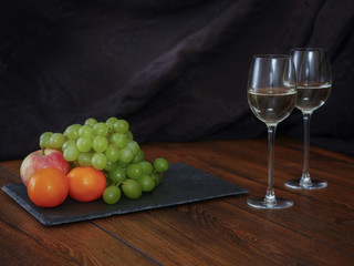 Still life: two glasses of white  wine and some fruits.