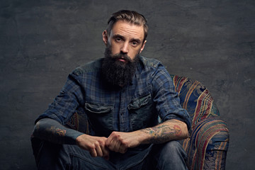 Tattooed bearded male sits on a chair.