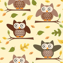 Seamless pattern with owls on a tree branch and autumn leaves on a yellow background