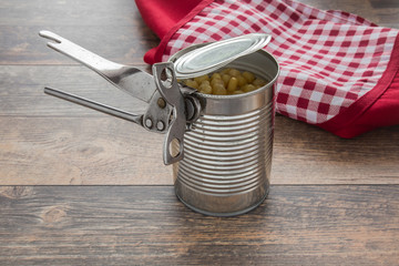 Old opener open to metallic can on the table in the kitchen. Canned corn in the can. Healthy eating and lifestyle.