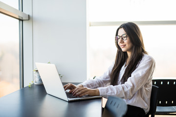 young woman worker sitting in office while using laptop computer and typing by keyboard