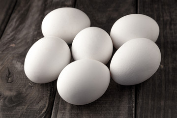 Raw fresh white farmer's eggs on wooden background. Healthy and sport food. Easter theme.