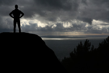 man against the sea standing on a mountain top looking into the distance