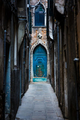 Narrow street and picturesque medieval door among old brick houses in Venice. Veneto, Italy