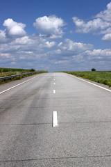 Asphalt road over blue sky background.