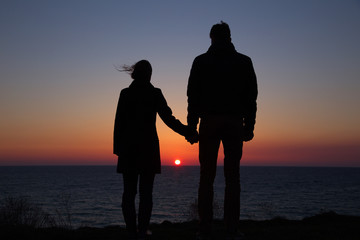 silhouette guy and girl on a beautiful sunset holding hands