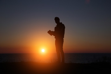 man reading an interesting book on the background of a beautiful sunset