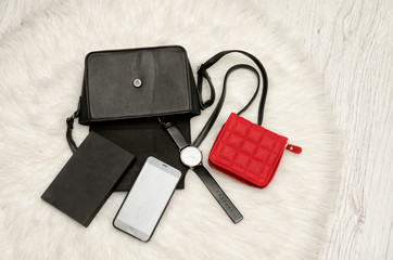 Open black bag with dropped things, notebook, mobile phone, watch and red purse. The white fur on background, top view. fashion concept