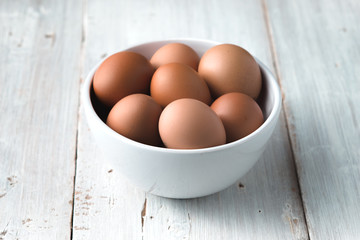 Chicken eggs  in the ceramic bowl on the white wooden table