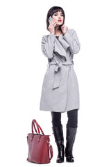 Young woman dressed in a gray coat talking on the phone